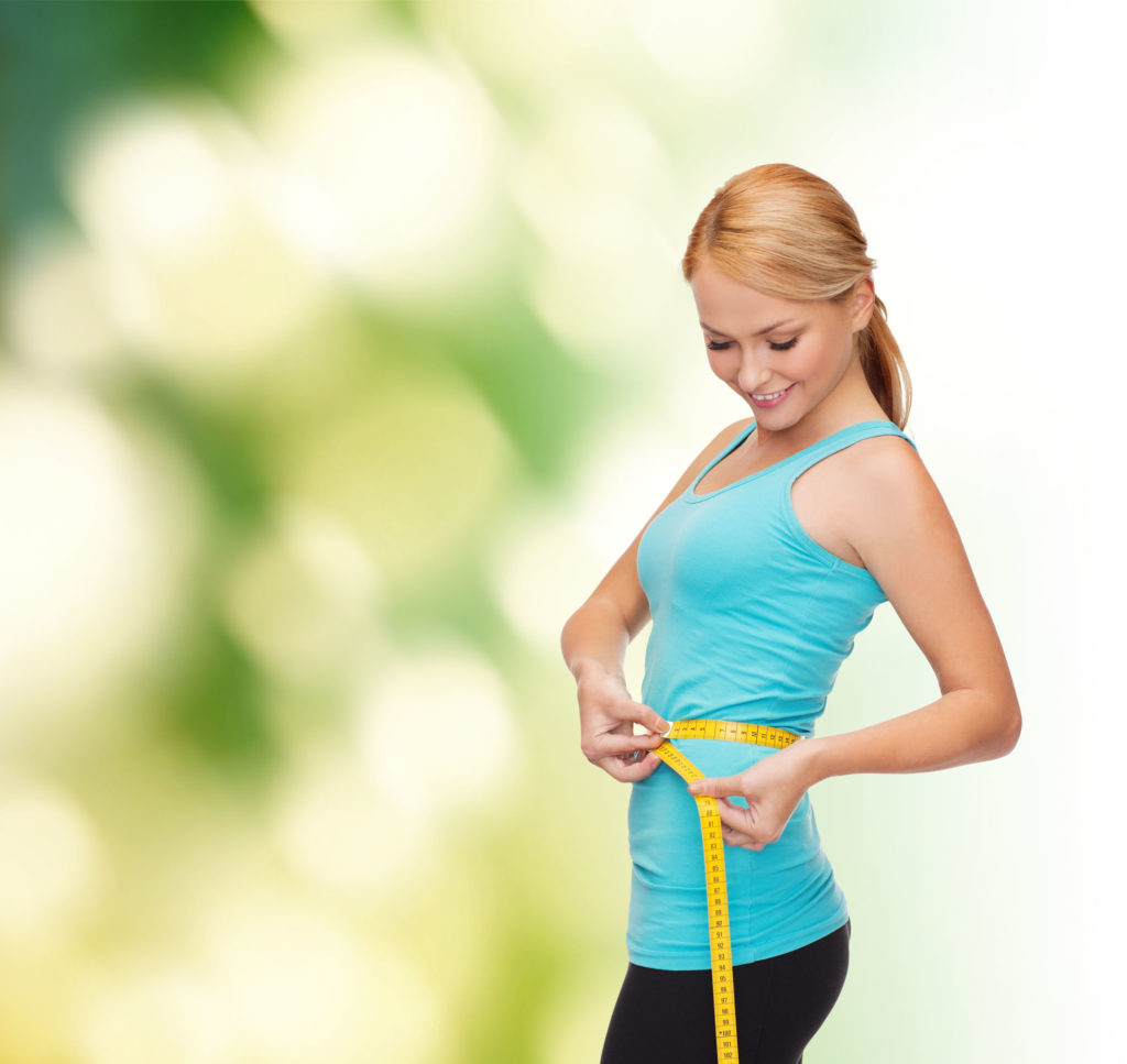 active woman measure waist with tape measure after using hypnosis for weight loss