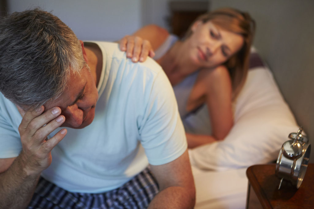 wife comforting husband at bedside and could benefit from using hypnosis to treat anxiety